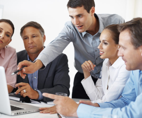 Business team discussing project with man pointing at the laptop